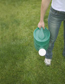 Low section of woman carrying watering can — Stock Photo