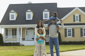 Portrait of family in front of house — Stock Photo