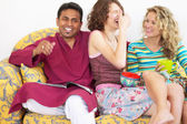 Friends laughing on couch — Stock Photo
