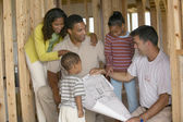 Family with contractor in unfinished house — Stock Photo