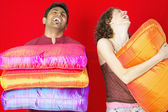 Couple laughing while holding pillows — Stock Photo