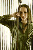 Portrait of woman holding bead curtain — Stock Photo