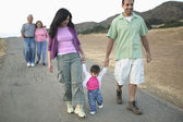 Family walking along paved pathway together — Stock Photo