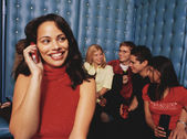 Young woman taking phone call in night club — Stock Photo