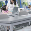 Female teacher helping girl on laptop - Stock Photo