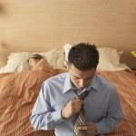 Businessman adjusting tie in bedroom — Stock Photo #23220308
