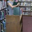 Portrait of librarian holding books - Stock Photo