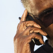Senior man wearing sunglasses speaking on phone - Stock Photo