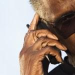 Senior man wearing sunglasses speaking on phone — Stock Photo