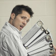 Portrait of man holding stack of notebooks — Stock Photo