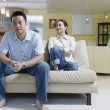 Couple sitting on couch — Stock Photo #23220592