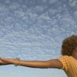 Young woman with outstretched arms - Stock Photo