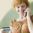 Woman talking on cell phone and holding credit card - Stock Photo