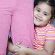 Portrait of young girl hugging mother's leg — Stock Photo