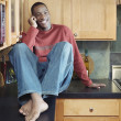 Man talking on cell phone in kitchen - Stock Photo