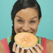 Portrait of woman holding cantaloupe - Stock Photo