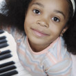 Portrait of girl sitting at piano — Stock Photo