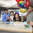 Woman blowing out birthday candles at office party — Stock Photo
