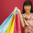 Portrait of woman holding gift bags — Stockfoto