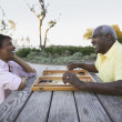 Senior couple playing game of backgammon — Stock Photo