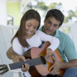 Father teaching daughter to play guitar — Stock Photo