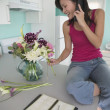 Young woman talking on phone in kitchen — Stock Photo