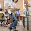 Young man on skateboard with files in hand - Stock Photo