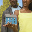Couple holding model of house — Stock Photo