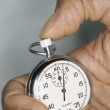 Close up of hand holding stop watch - Stock Photo