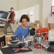 Young woman admiring kitchenware while partner moves tv — Stock Photo