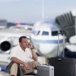 Businessman talking on cell phone at airport — Stock Photo