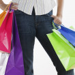 Young man holding brightly colored shopping bags — Foto Stock