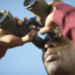 Stock Photo: Young mlooking through binoculars
