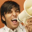 Man shouting through bull horn - Stock Photo