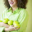 Woman holding apples while laughing - Stock Photo