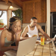 Couple in kitchen reading newspaper and working on laptop — Stock Photo
