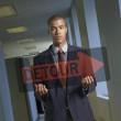 Portrait of businessman holding transparent detour sign - Stock Photo