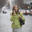 Woman walking down street talking on cell phone - Lizenzfreies Foto