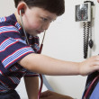 Young boy listening to doctor's heart with stethoscope — Foto Stock