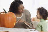 Mother and daughter carving pumpkin — Stock Photo