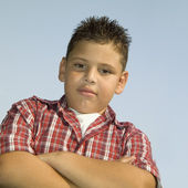 Low angle view of a young boy standing with his arms folded — Stock Photo