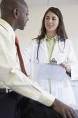 Vrouwelijke arts in gesprek met zakenman — Stockfoto