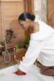 Woman preparing bath water in bathroom — Stock Photo
