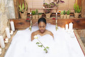 Woman in bubble bath with rose — Stock Photo