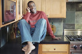 Man talking on cell phone in kitchen — Stock Photo