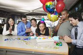 Woman blowing out birthday candles at office party — Stok fotoğraf
