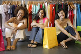 Portrait of women sitting in clothing store — Stock Photo