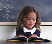 Young school girl reading at desk — Stock Photo