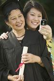 Imagen de chica de tomar de la madre en la graduación — Foto de Stock