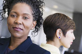 Close-up of a two businesswoman standing with their backs towards each other — Stockfoto